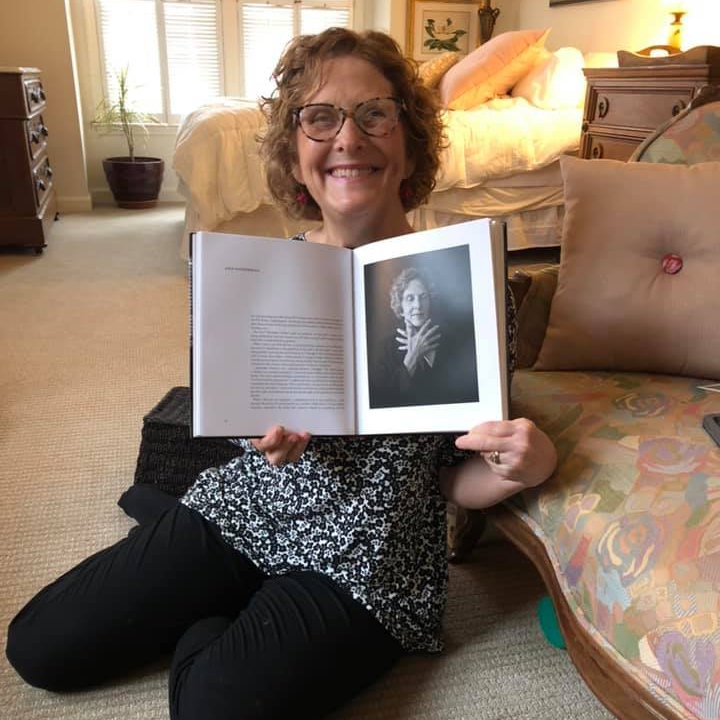 Ann holding a copy of My Heart is Not Blind with the pages opened to the portrait of her. She's relaxed on the floor and leaning against the couch. She has a big smile.