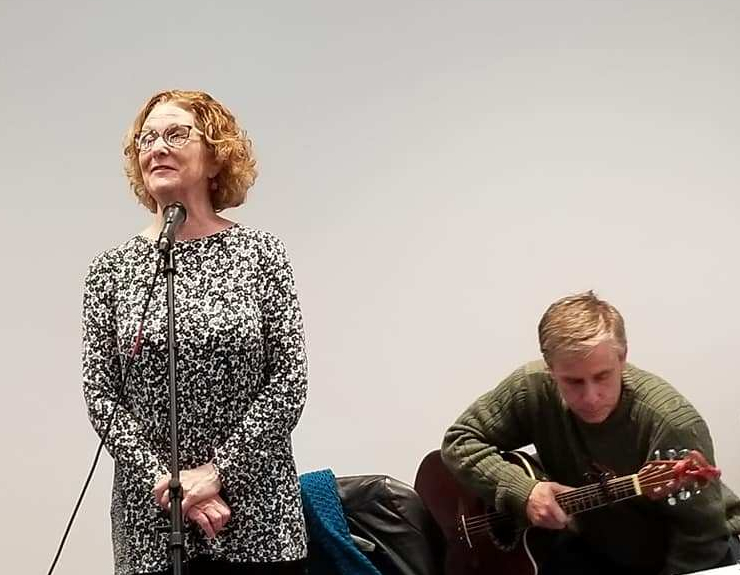 Ann at a poetry recitation. She's standing at the mic and there's an accompanying guitarist seated to her right.