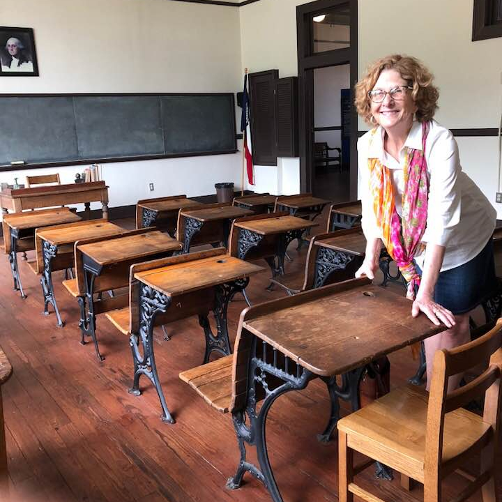 Ann is in an old classroom. The room has a chalkboard and multiple wooden desks. She's standing and leaning over one of the desks and smiling.