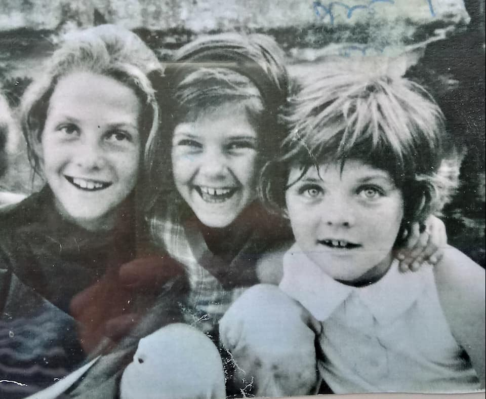 Ann and her two sisters, Mary and Cindy, as little girls. It's a black and white photo with all three girls facing the camera with their heads close together. Ann is on the far left and looks about 10 years old. Her sister, Mary, is in the middle and Cindy is on the far right. They're on the banks of the Frio River in Leakey, Texas.