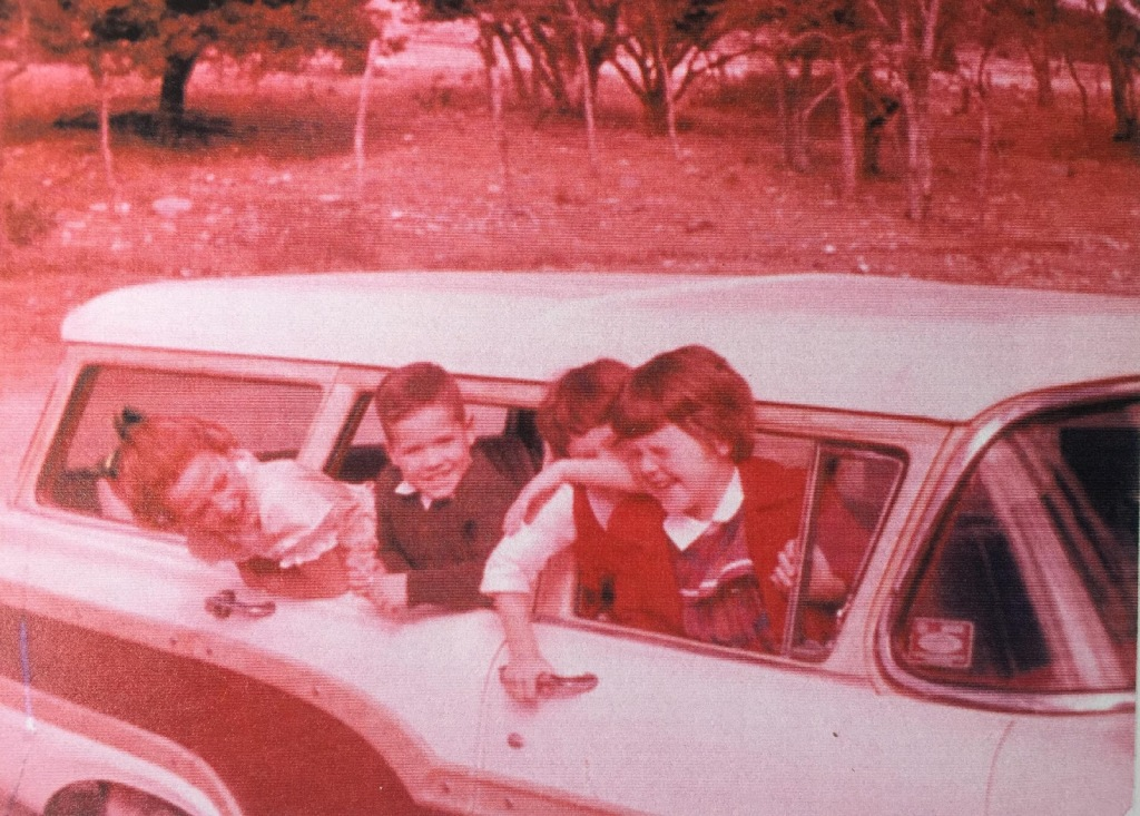Old photo of Ann and her siblings when they were young. Ann and her two sisters and brother are sticking their heads out of the passenger side windows of a station wagon. The background is Texas hill country with scrub brush and limestone rocks on the ground.