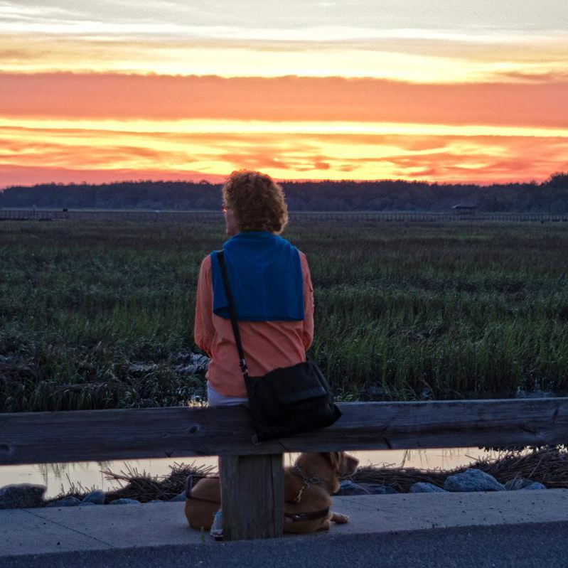 Ann and Brego at Huntington Beach State Park at the beginning of a new day. Beautiful orange and yellow sunset in the background as Ann sits on a railing with Brego at her feet. Photo by Sparkle Clark.