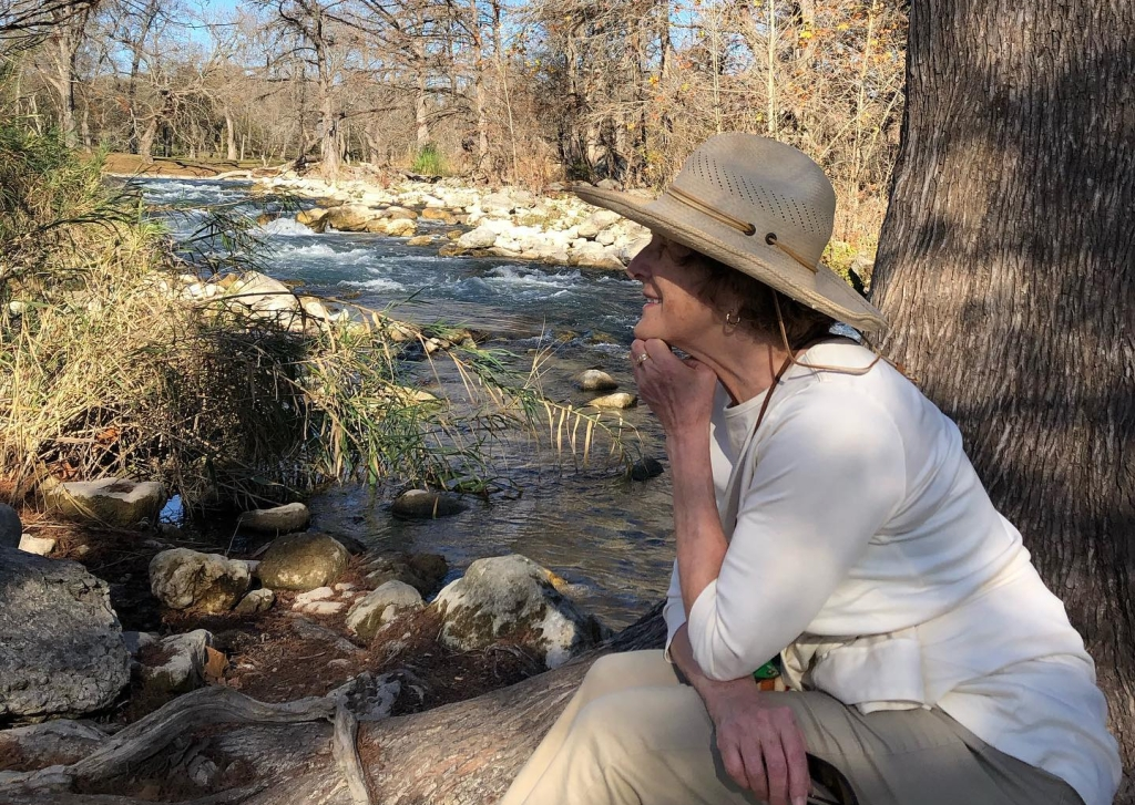 Ann sits by the Guadalupe River in Gruene, Texas. Photo by Mary Seaborne, Ann's sister.